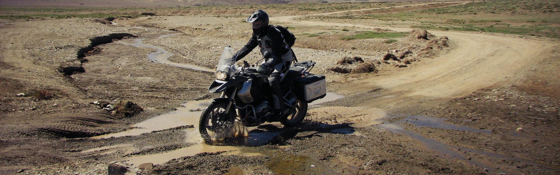 Motorradfahrer fährt durch Schlamm